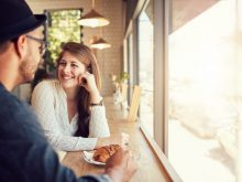 An attractive young woman talking with her boyfriend while sitting in a cafe table. Young couple at coffee shop.